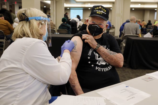 Ruth Mansheim, a registered nurse at Great River Health, gives Swede Johnson a COVID-19 vaccine shot Feb. 10 during a Des Moines County Public Health Department COVID-19 vaccination clinic at Burlington Memorial Auditorium. DMCPH will host another clinic today for persons 65 and older.