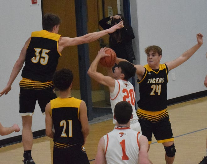 New London's Devin Swanson (24) and Kade Benjamin defend a Springville shot Tuesday. Swanson scored a career-high 34 points in the Tigers' 71-68 overtime win at West Liberty.