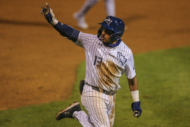 University of North Florida shortstop Abraham Sequera waves to his teammates on the bench as he rounds third following one of his two home runs on Tuesday in a 9-6 loss to the University of Florida.