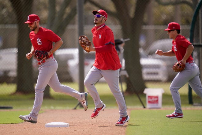 St. Louis Cardinals infielder Nolan Arenado, center, jogs out to the field with teammates Paul DeJong, left, and Tommy Edman during spring training baseball practice Monday, in Jupiter, Fla.