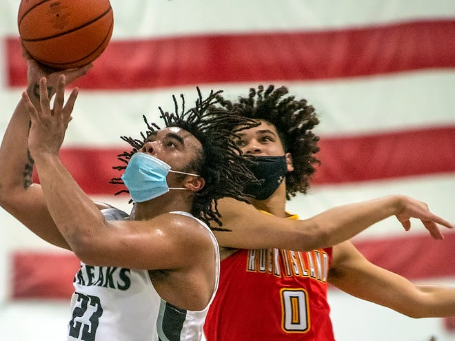 Galesburg senior Eric Price, left, gets past Rock Island's Eli Reese for a layup attempt during the Silver Streaks' 70-60 home WB6 Conference loss to the Rocks on Tuesday night, at the GHS field house.