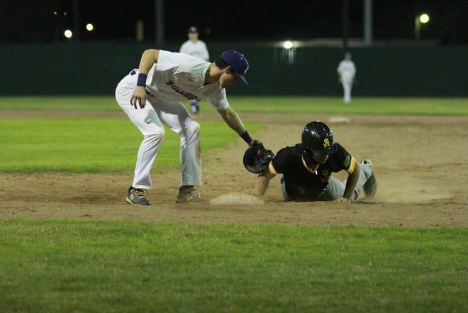 St. Amant's Blake LeBouef slides into first base, avoiding the tag of Ascension Catholic's Joel Landry