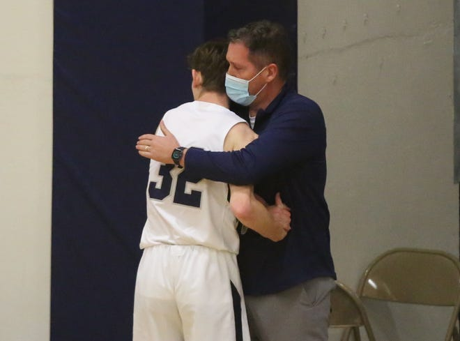 TMP's Jackson Schulte hugs his father, TMP athletic director Troy Schulte, after Jackson reached the 1,000-point milestone on Tuesday.