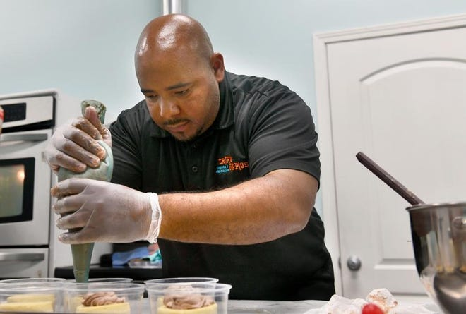 Triple Dipple's owner Harreld Webster adds the topping to a Kit Kat cheesecake in his Chillicothe bakery.