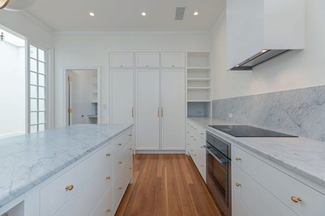 In the kitchen, the counters encompass copious cabinet, drawer and pantry storage with brass hardware, a Thermador smooth-top electric range, stainless sink with a brass gooseneck faucet, a cabinet-hidden dishwasher and Sub-Zero refrigerator.