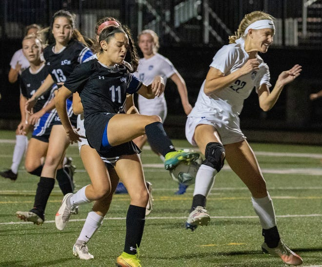 Lakeland Christian's Maddie Lopez tries to control the ball in front of Berkeley Prep's Carsyn Martz on Tuesday night in the Class 3A, Region 2 girls soccer finals at Viking Stadium.
