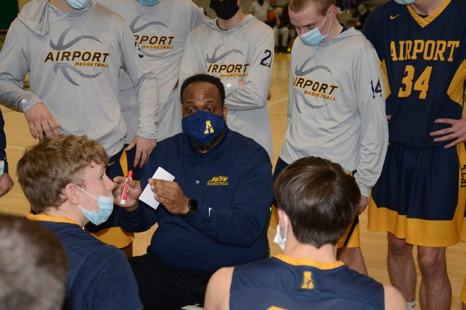 Airport coach Don Spencer talks to his team during a 50-35 win over Flat Rock Tuesday night.