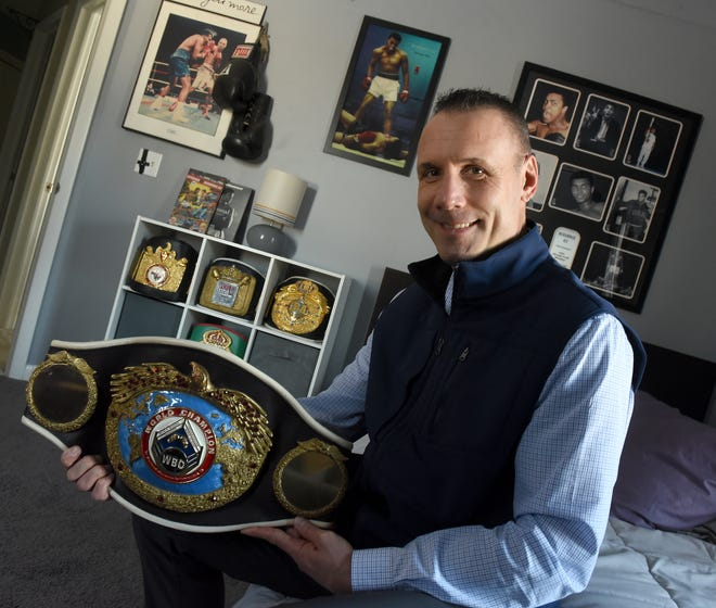 Bronco McKart of Monroe holds up his WBO World Championship belt which he earned March 1, 1996 after by beating Santos Cardona in California. The pictures on his wall are of his idol Muhammad Ali.