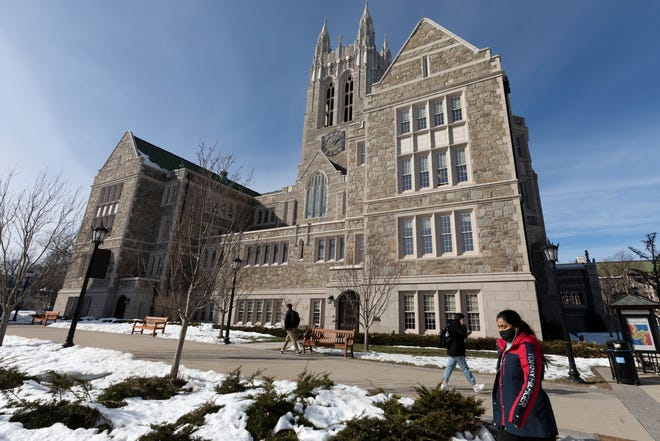 Students walk on the Boston College campus on Feb. 17, 2021. President Joe Biden campaigned on multiple tuition-free college proposals. But experts are divided on whether now is the time students could see a broad free college program. [AP File Photo/Michael Dwyer]