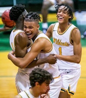 Forest's Elijah Russell and Jeremiah Russell celebrate after Brenen Lorient dunked over a Fletcher defender. The Wildcats defeated the Fletcher Senators, 63-50, Tuesday night in the Class 6A, Region 1 semifinals.