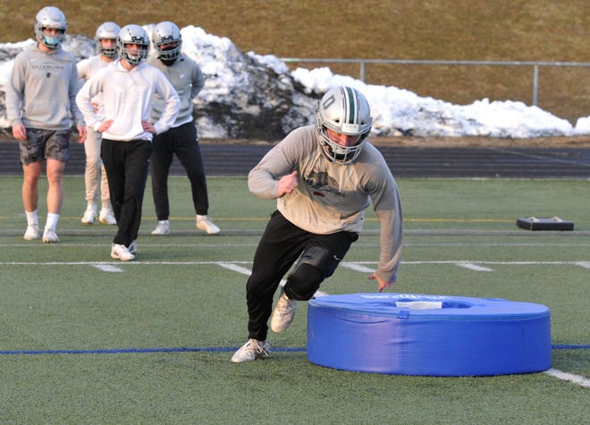 Duxbury middle linebacker Tim O'Neil, one of the team's four senior captains, participates in a conditioning drill during football practice at Duxbury High School, Tuesday, Feb. 23, 2021.