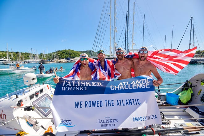 Pictured left to right:  Jimmy Carroll, Jono Mawson, Todd Hooper and Dixon McDonald hold up a sign after finishing the Talisker Whiskey Challenge race across the Atlantic Ocean. (Courtesy: Dixon McDonald)