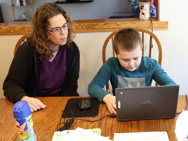 Lauren Tomaszewski-Schiebel's 9 year old son, Brandon, is in third grade and sits at the kitchen table for remote learning on his laptop as part of the Kennebunk school district's hybrid approach.