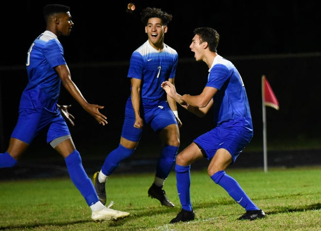 Spanish River forward Tyler Jones (18) hi-fives teammates Tomas Gomez (7) and Isaac Schweiger (14) after scoring the first goal of the game Tuesday in the Region 3-Class 7A boys soccer final against Port St. Lucie-Centennial in Boca Raton.