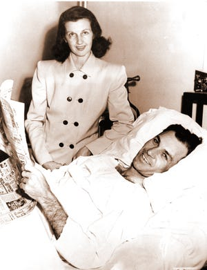 Ben Hogan, one of the nation's leading golfers, smiles from his hospital bed at El Paso on Feb. 12, 1949.  Hogan was recovering from injuries suffered when his automobile collided with a bus Feb. 2.  With him was his wife, Valerie, who suffered bruises. Hogan suffered a fractured pelvis, fractured collarbone, a broken bone in his ankle, a cracked rib and multiple bruises.