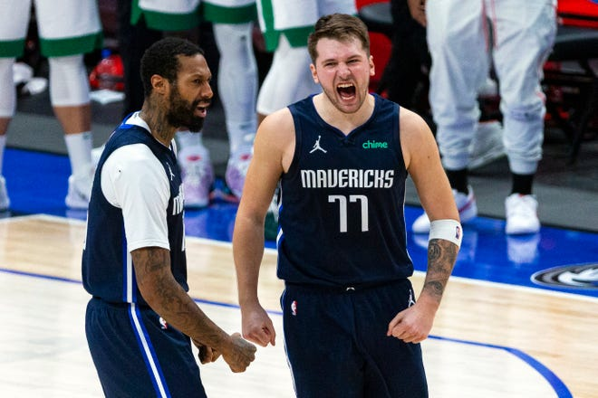 Dallas Mavericks guard Luka Doncic (77) celebrates with teammate James Johnson (16) after making a 3-point basket during the second half against the Boston Celtics in Dallas, Tuesday, Feb. 23, 2021.