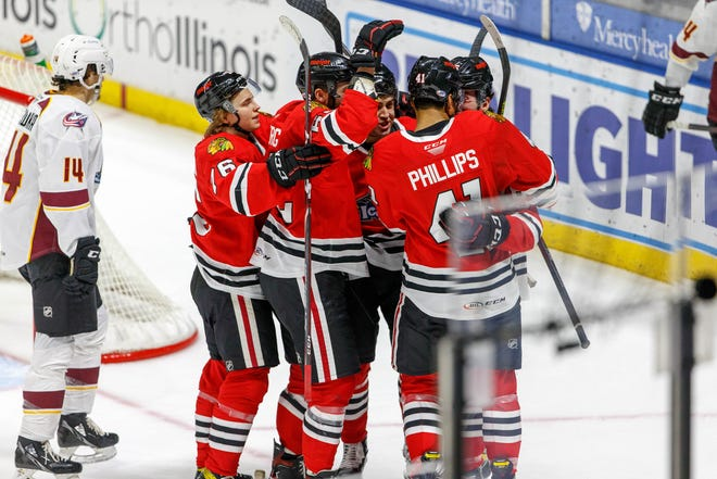 Rockford IceHogs players swarm Isaak Phillips after he scored the eventual game-winning goal with 1:57 left to play on Tuesday, Feb. 23, 2021, in Rockford. The IceHogs notched their first win with a pair of goals in the final 3:23.