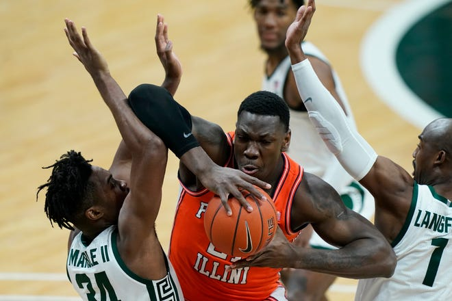 Illinois center Kofi Cockburn (21) is defended by Michigan State forward Julius Marble II (34) and guard Joshua Langford (1) during the first half of A Big Ten college basketball game on Tuesday, Feb. 23, 2021, in East Lansing, Mich.