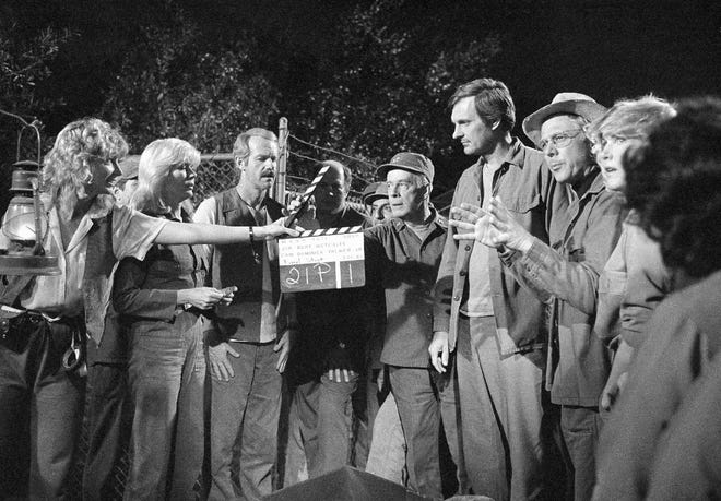 """A crew member holds up a clacker as the cast of """"M-A-S-H"""" films the final episode of the hit television series in Los Angeles on Jan. 14 1983. From left are Loretta Swit, Mike Farrell, David Ogden Stiers, Jamie Farr, Harry Morgan, Alan Alda and William Christopher. The last episode of """"M-A-S-H"""" aired on CBS on Feb. 28, 1983, concluding the seventh and final season."""