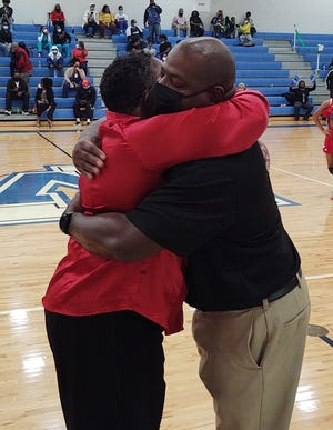 Dodge County girls basketball coach CaSandra Hamilton, left, and her younger brother, Woodville-Tompkins coach Jeffery Roberson, hug after the game won by the host Wolverines 48-36 on Tuesday night in the first round of the GHSA Class 2A playoffs.