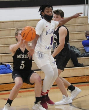 Meeker's Josh Caldwell (left) attempts to deliver a pass against the defense of Millwood's William Mays (1) Tuesday night in Class 3A district play at McLoud. Also pictured for Meeker is Caleb Chapman (13).