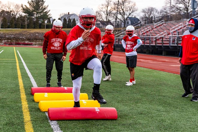 New Bedford's Jose Bonilla does high knee's through the pads at preseason training.