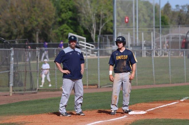 UMass Dartmouth baseball coach Bob Prince (left) stands at third base.