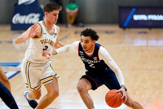UConn's James Bouknight, right, dribbles past Villanova's Collin Gillespie during the Huskies' recent loss  in Villanova, Pa.