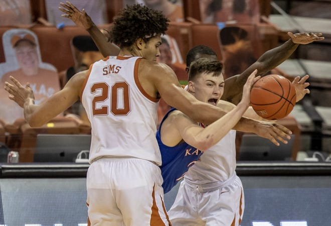 Kansas guard Christian Braun looks to pass the ball as Texas forward Jericho Sims, left, and guard Andrew Jones defend during the second half of Tuesday's game in Austin, Texas. The No. 17-ranked Jayhawks fell 75-72 in overtime.