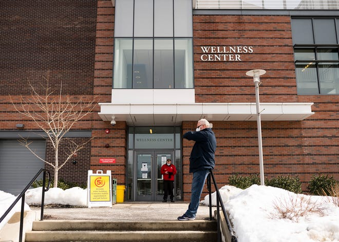 David Demanche, of Uxbridge, checks his watch while waiting for the COVID-19 vaccination clinic to open at Worcester State University on Wednesday.