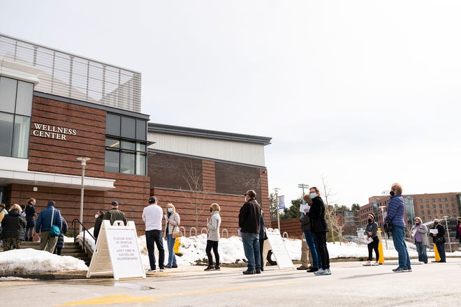 Patients wait in line ahead of their appointments for the COVID-19 vaccination Wednesday at Worcester State University.