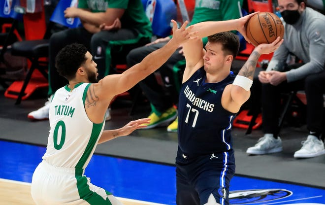 Mavericks guard Luka Doncic looks to pass as Celtics forward Jayson Tatum defends during the first quarter Tuesday night in Dallas.