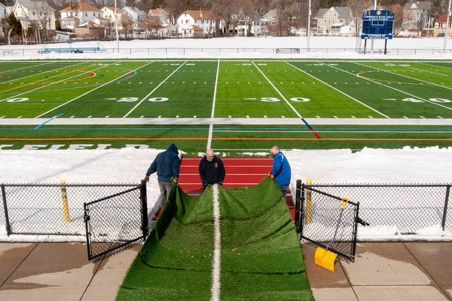 School department workers clear snow from Commerce Bank Field at Foley Stadium on Wednesday. Here, they are pulling a mat that protects the track from football cleats.