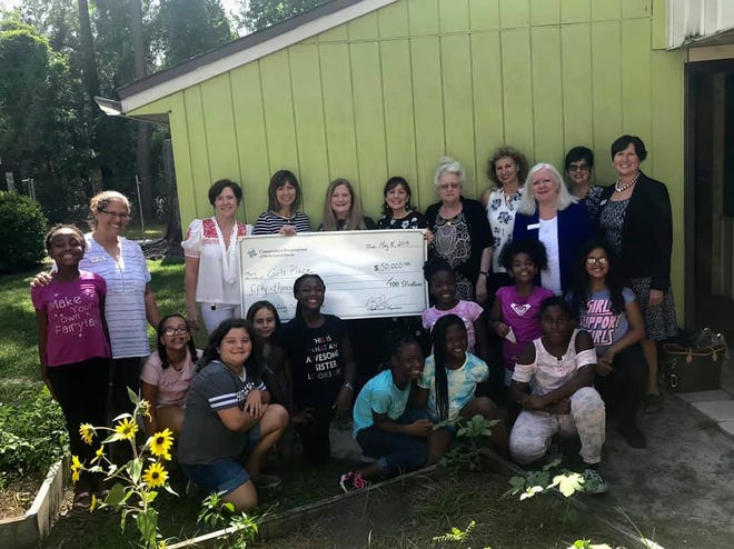 Members of the Giving Circle present Girls Place with the funds to expand their classroom capacity.