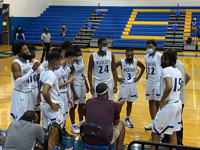 Coach Joseph Spinks, middle, relays instructions to his Eastern Guilford team in a timeout huddle during Tuesday night's first-round state playoff game against East Wake.