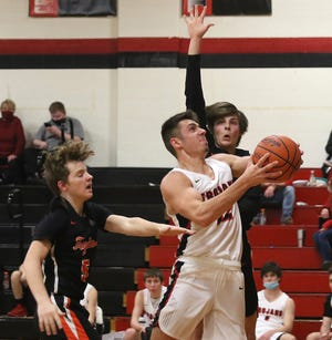 Tusky Valley's Jayson Hall drives the ball to the basket as Newcomerstown's David Dunigan and Braxton Wilson defend in the Division III Sectional game Tuesday.