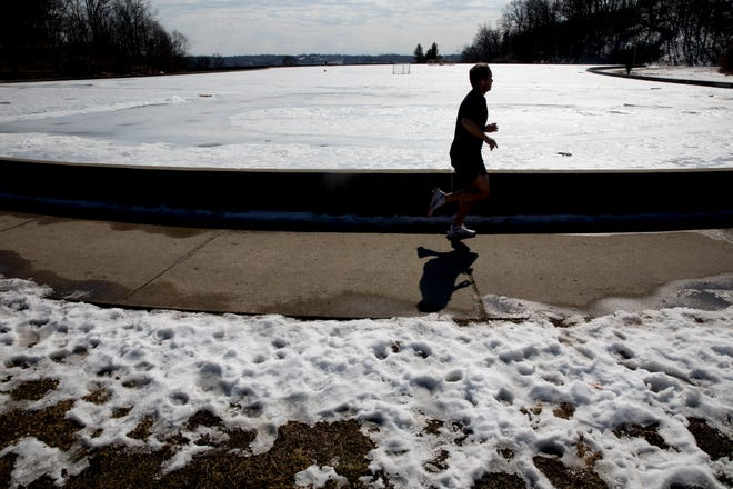 A pedestrian runs around Mirror Lake at Eden Park in Mt Adams on Wedesday, Feb. 24, 2021. The National Weather Service expects the high temperature to reach 65 degrees on Wednesday.