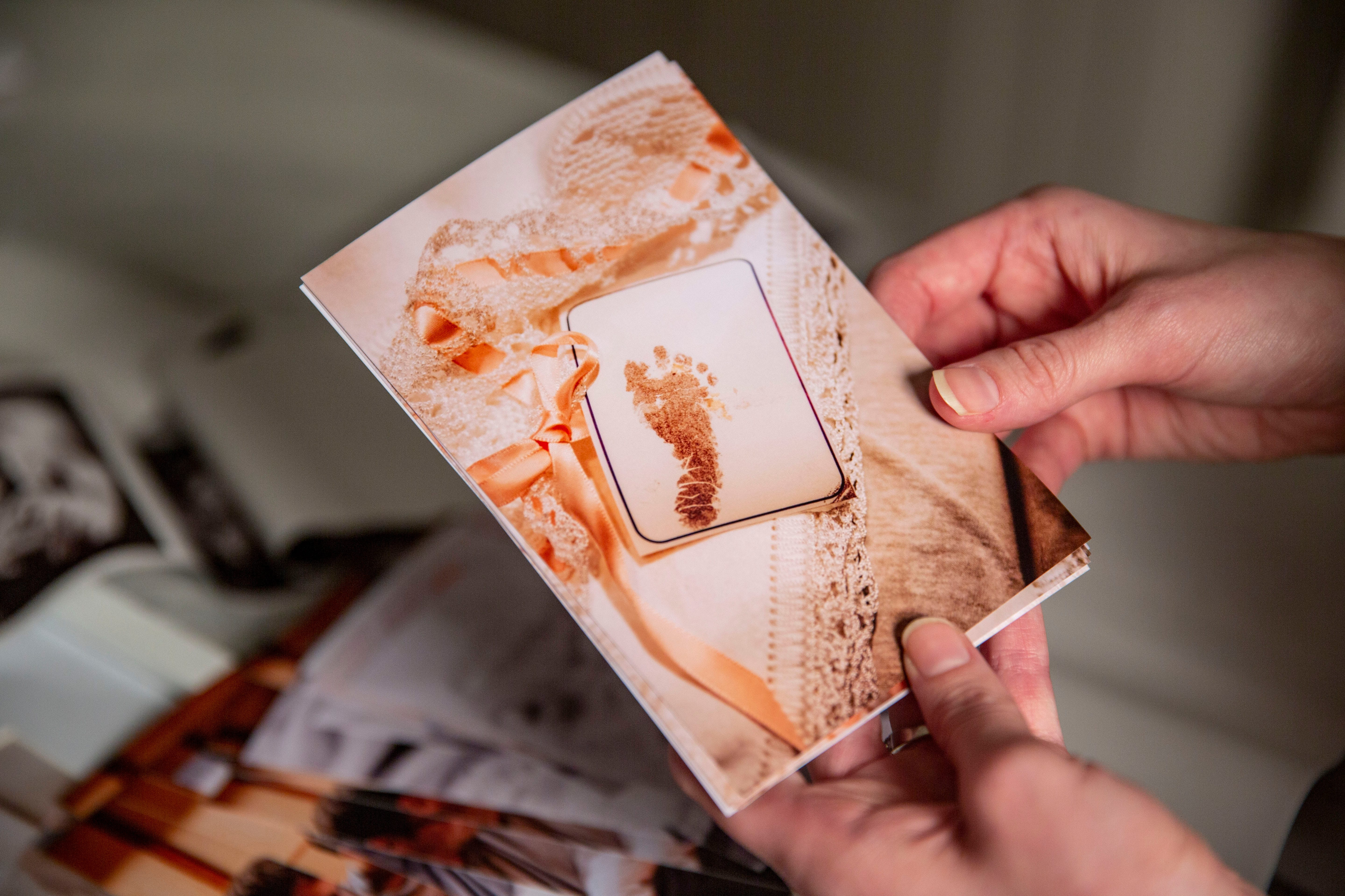 McKenzie Harreld looks at photos taken by nurse Cherish Shuka of her daughter Blakely's footprint after she gave birth to her and her son, Calvin, at Mary Greeley Medical Center in Ames. Blakely was stillborn, and Shuka volunteered to photograph the family together so that the Harrelds would have something to help remember her.