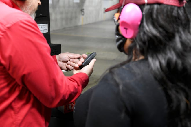 Thondra Jeter watches as an instructor loads a pistol magazine. The instruction was part of a conceal carry class held by the National African American Gun Association at Crossroads Shooting Sports in Johnston, Iowa. The Kansas Legislature passed a bill lowering the age for concealed carry.