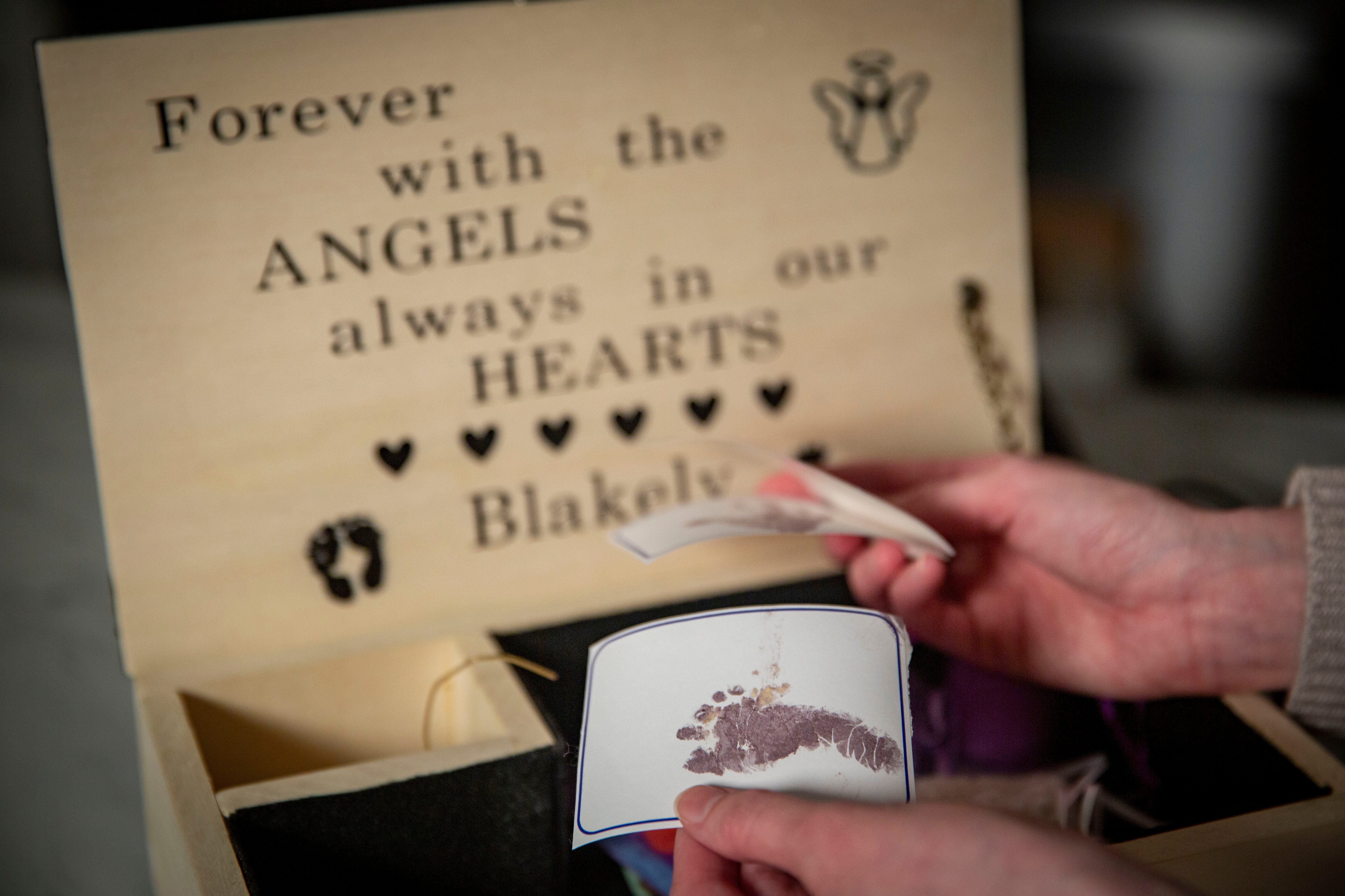 McKenzie Harreld looks at her daughter Blakely's footprint, which she keeps with other mementos in a handcrafted box her dad made.