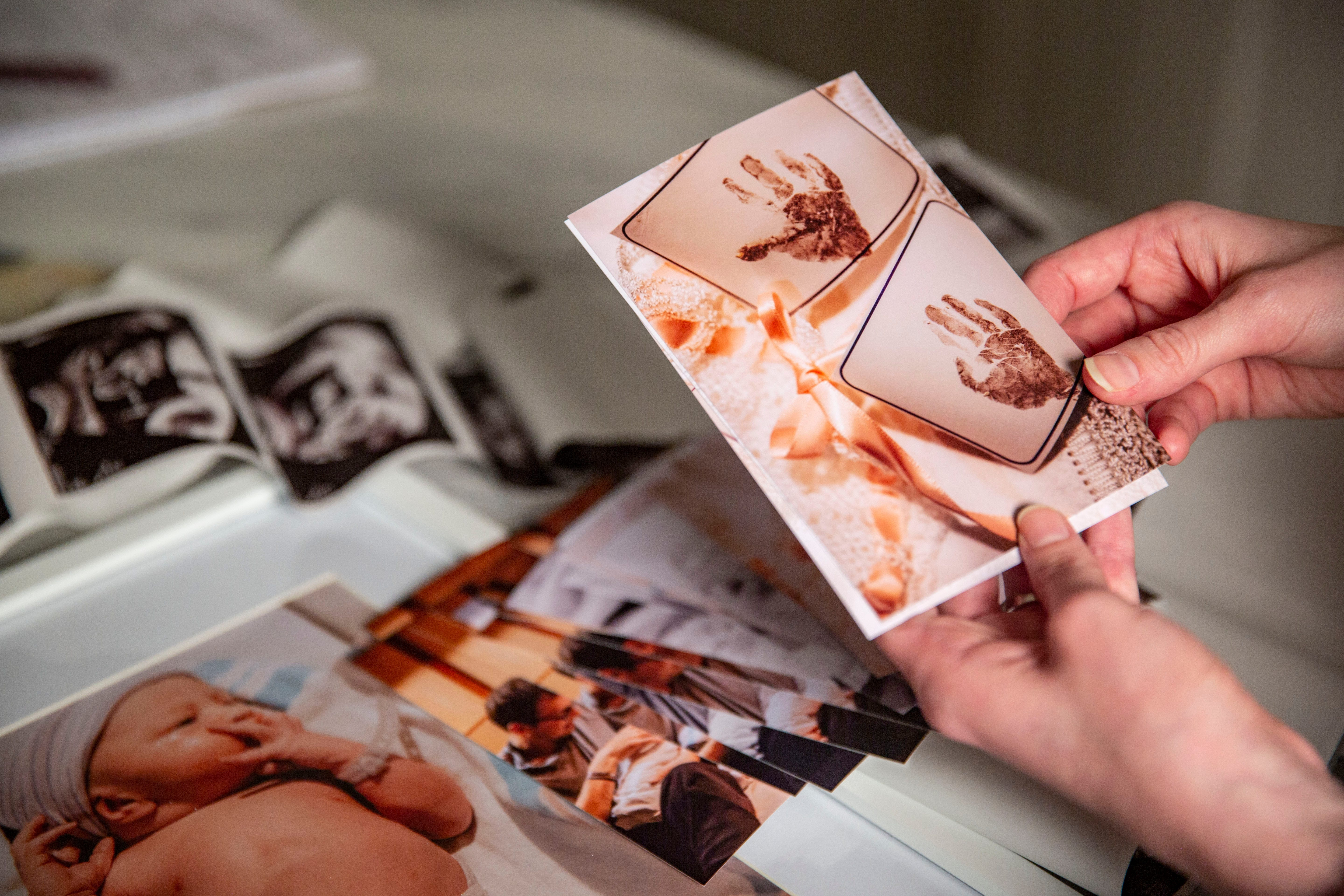 McKenzie Harreld looks at photos taken by nurse Cherish Shuka of her daughter Blakely's handprints after she gave birth to her and her son, Calvin, at Mary Greeley Medical Center in Ames. Blakely was stillborn, and Shuka volunteered to photograph the family together so that the Harrelds would have something to help remember her.