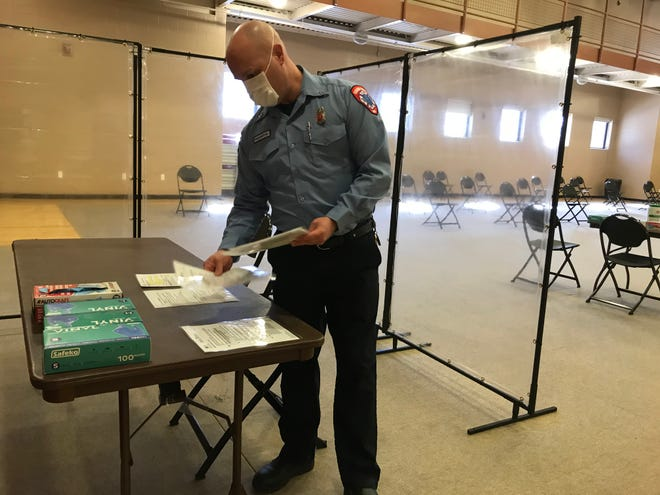 Sterling Heights Fire Capt. Will Walker sets up a station at a new vaccination clinic for senior citizens in Macomb County in the Sterling Heights Senior Center on Feb. 24, 2021.