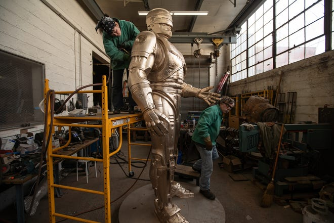 Nadine Chronopoulos, left, grinds and sands an 11-foot RoboCop statue on Feb. 24 at a warehouse on Detroit's east side. Jay Jurma walks around the statue. The statue will be housed somewhere while waiting for a home to be announced.