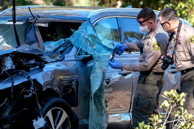 Law enforcement officers look over a damaged vehicle following a rollover accident involving golfer Tiger Woods.