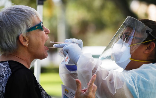 Joceline Saunders, right, a disease intervention specialist, administers a COVID-19 test for Deanna Thomas, Sept. 17, at a Fort Myers walk-up COVID-19 test site in Yawkey Park.