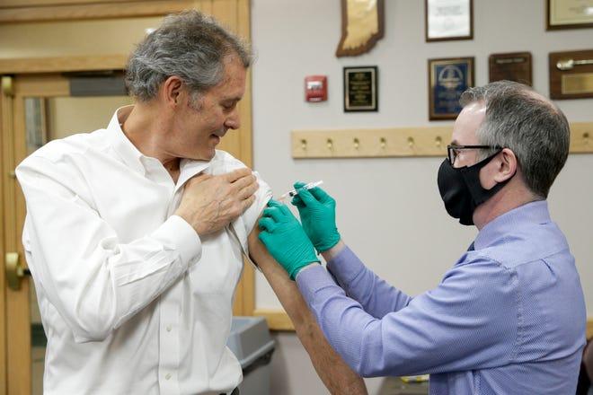 West Lafayette Mayor John Dennis receives the Moderna COVID-19 vaccine shot from Dr. Jeremy Adler, Tippecanoe County's health officer, Wednesday, Feb. 24, 2021 in Lafayette.