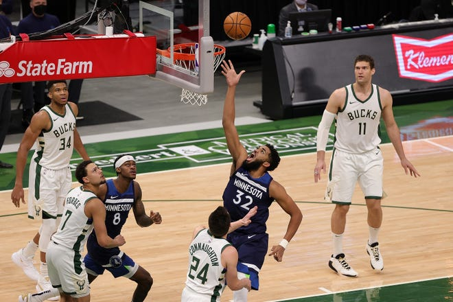 Giannis Antetokounmpo (far left) watches as  Minnesota's Karl-Anthony Towns finishes a drive in front of Bucks guard Pat Connaughton. Towns and Antetokounmpo have become friends.