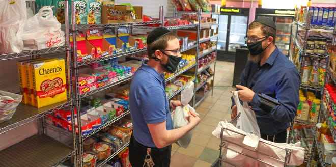 Mordechai Bates, left, the owner of QuicKosher market, and Avi Slutzkin, store manager, discuss a customer's order before bagging items.
