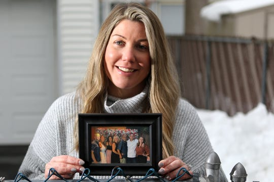 Meagan Cappa, of Wayne, spent approximately a month going online every chance should could to secure COVID-19 vaccines for her parents and grandparents. Here she poses with a picture of her family, including her parents,  Lisa Cappa (4th from left) and Frank Cappa (5th from left). Tuesday, Feb. 23, 2021