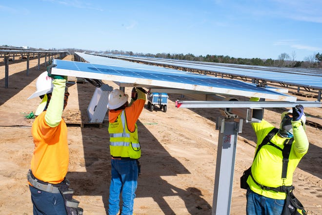 Gulf Power construction workers install a solar panel at the Blue Indigo Solar Energy Center in Jackson County on Jan 7, 2020.